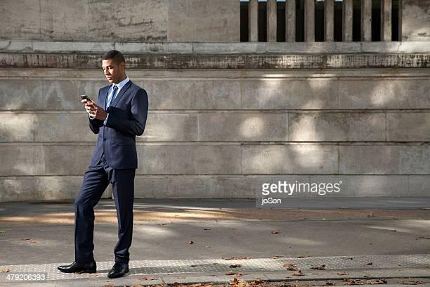 Businessman using mobile phone on a sidewalk