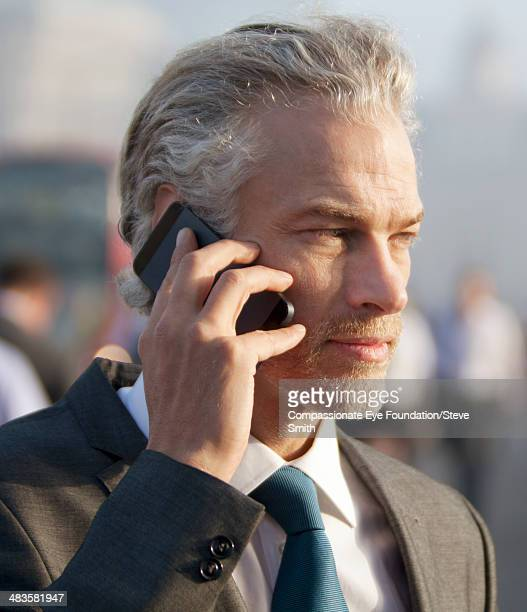 Businessman using mobile phone on city street