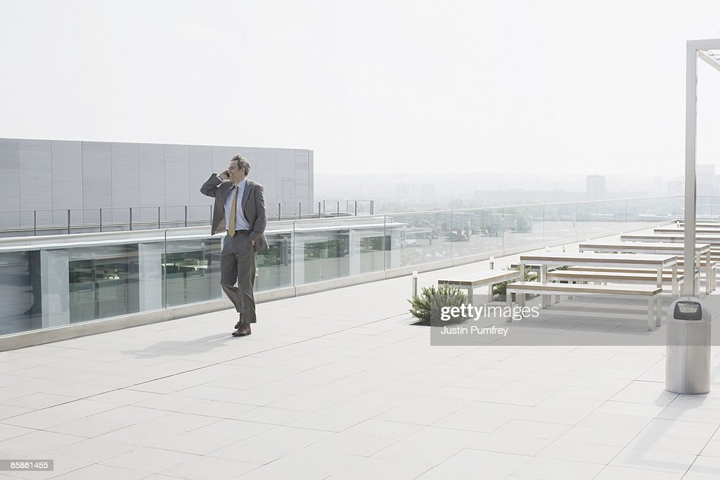 Businessman using mobile phone on rooftop : Stock-Foto