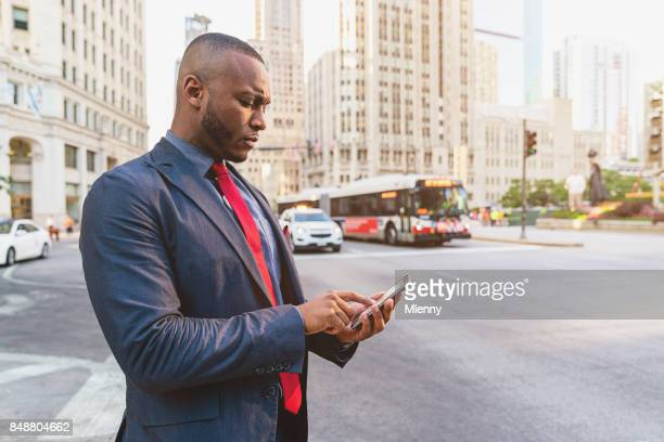 Businessman using mobile phone taxi app to get a cab in Chicago