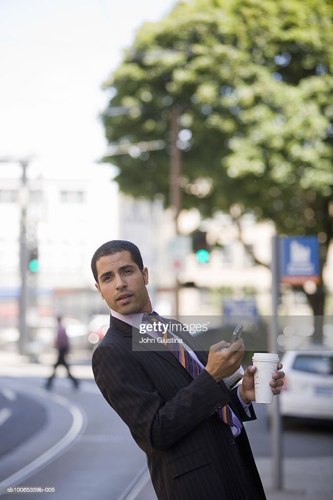 Businessman using mobile phone waiting on city street : Foto stock
