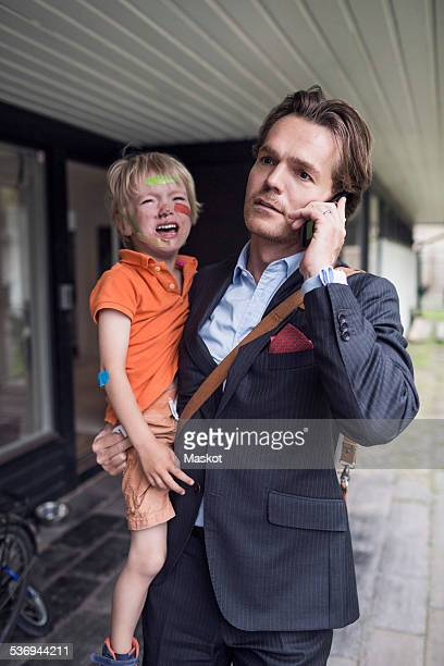 Businessman using mobile phone while carrying crying son outside house
