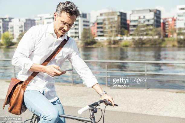 businessman using mobile phone while cycling bicycle on sunny day - hesse duitsland stockfoto's en -beelden