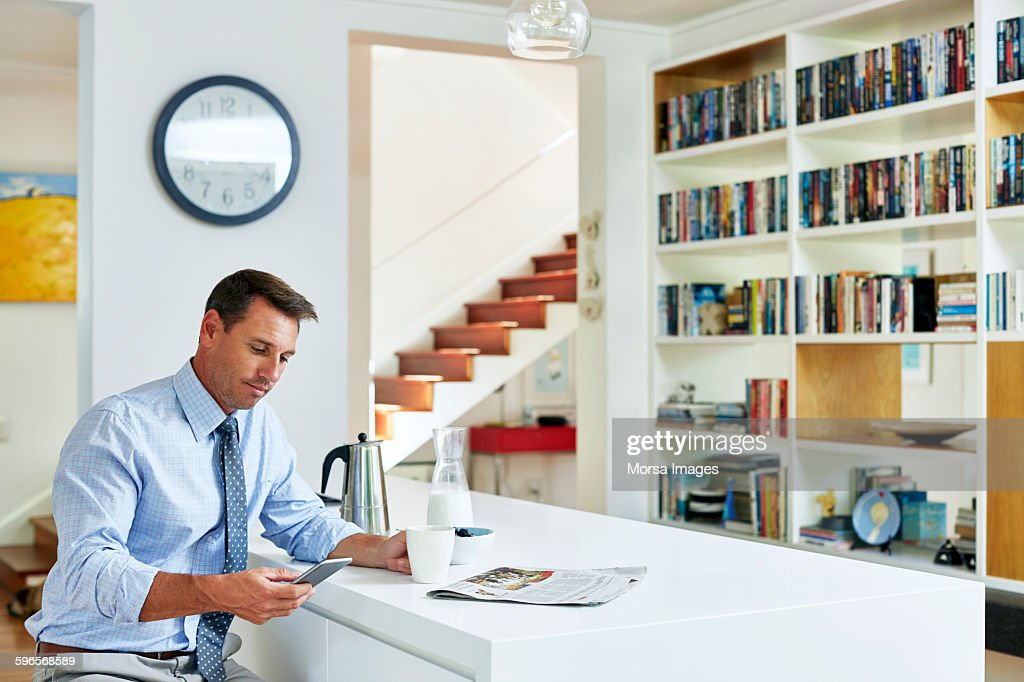 Businessman using mobile phone while having coffee : Stock Photo