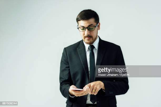 Businessman Using Mobile Phone While Standing Against White Background