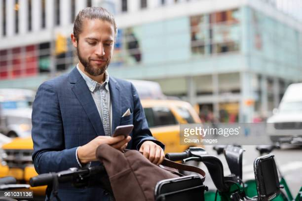 businessman using mobile phone while standing at parking lot - bicycle parking station stock photos and pictures