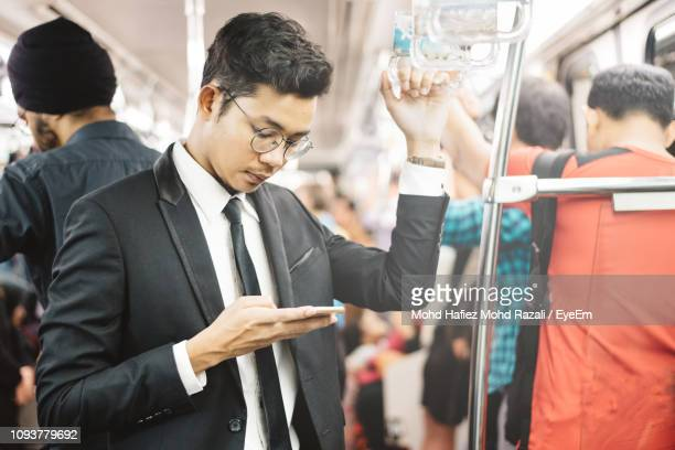 businessman using mobile phone while standing in train - 鉄道 ストックフォトと画像