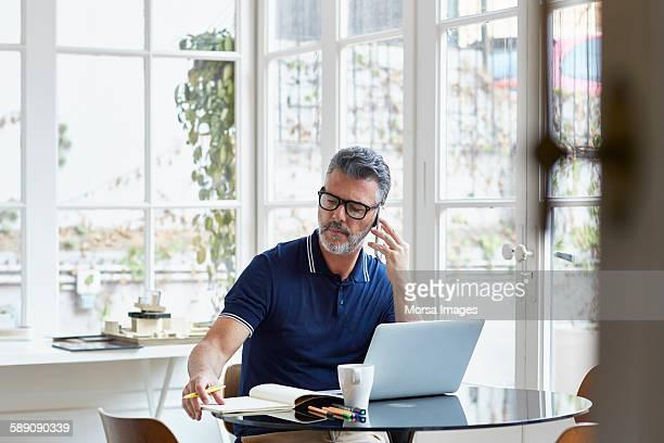 businessman using mobile phone while writing notes - usare il telefono foto e immagini stock