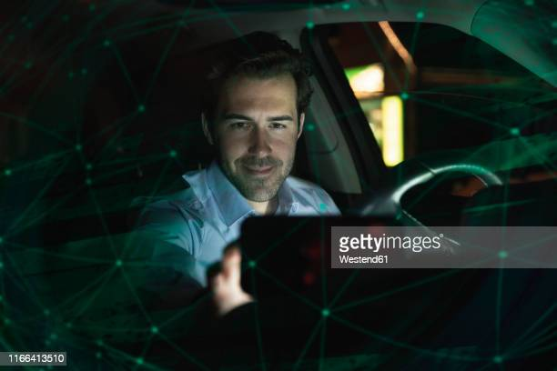 businessman using navigation device in car at night - transportation occupation stock pictures, royalty-free photos & images