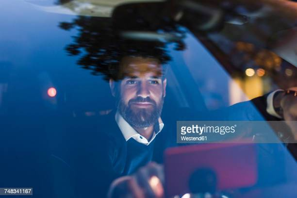 businessman using navigation device in car at night - driver stock pictures, royalty-free photos & images