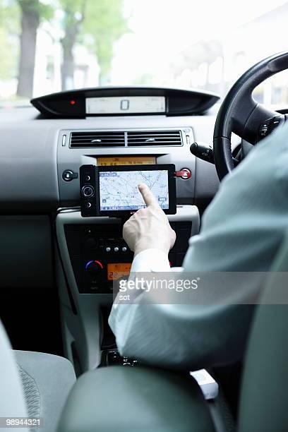 Businessman using navigation system in car