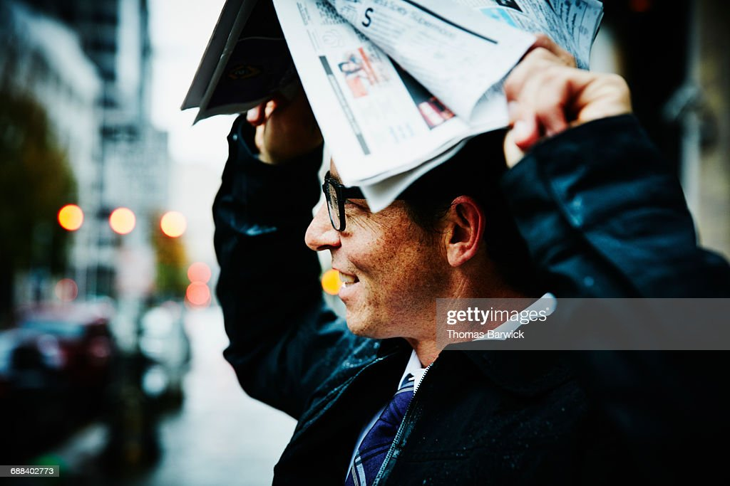 Businessman using newspaper to protect from rain : Stock Photo