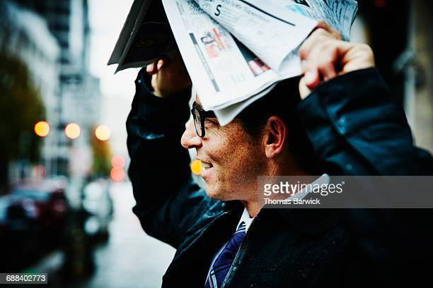 Businessman using newspaper to protect from rain