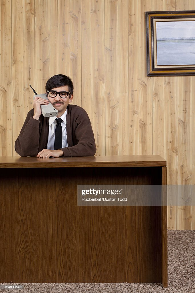 Businessman using old fashioned mobile phone in office : Stock Photo