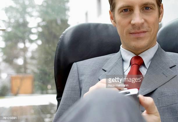 Businessman using palmtop, portrait