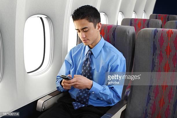 Businessman Using PDA On Airplane
