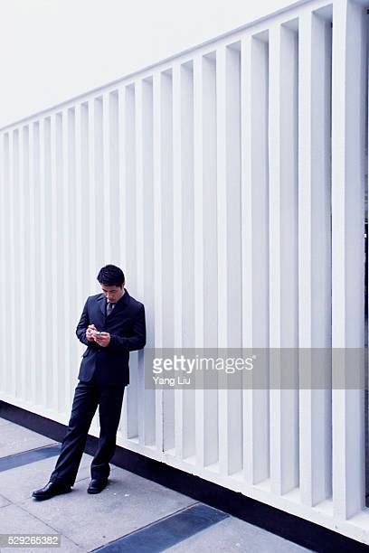businessman using personal digital assistant - liu he stock pictures, royalty-free photos & images