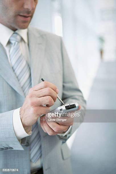businessman using personal digital assistant - oliver eltinger stock-fotos und bilder