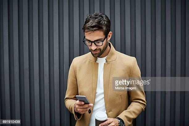 Businessman using phone and holding cup in city
