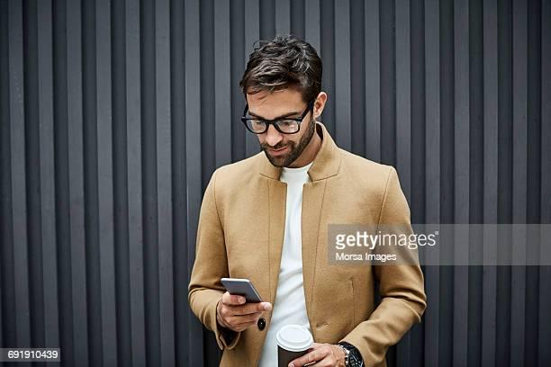businessman using phone and holding cup in city - guardare verso il basso foto e immagini stock