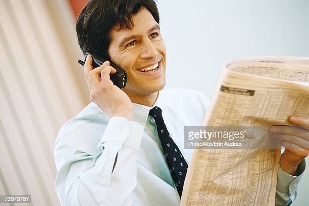 businessman using phone and holding up financial section of newspaper, smiling - shareholder stock pictures, royalty-free photos & images