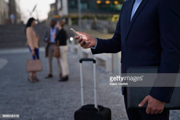 Businessman using phone at taxi pickup station