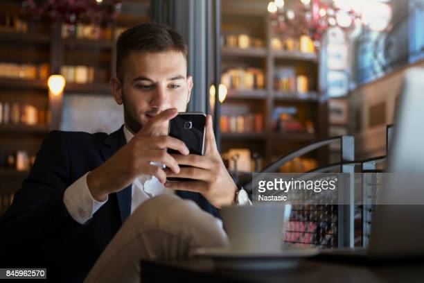 Businessman using phone for texting massage