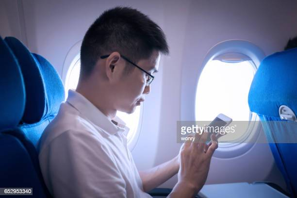 Businessman using phone in airplane travelling