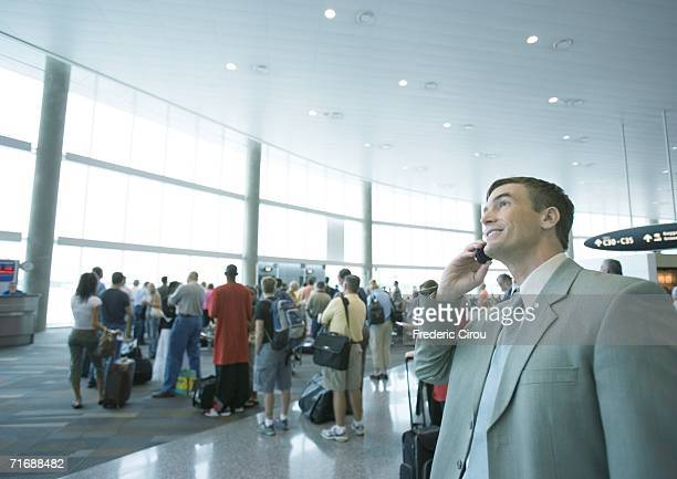 Businessman using phone in airport boarding area