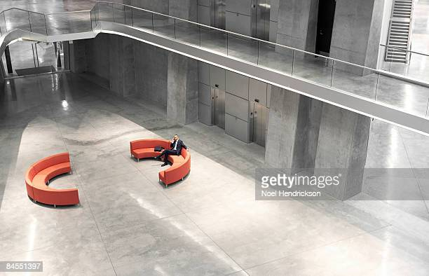 businessman using phone in large modern interior
