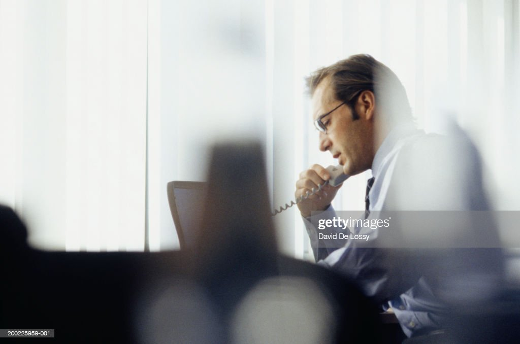 Businessman using phone in office : Stock Photo