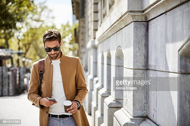 businessman using phone while holding cup in city - brown jacket stock pictures, royalty-free photos & images