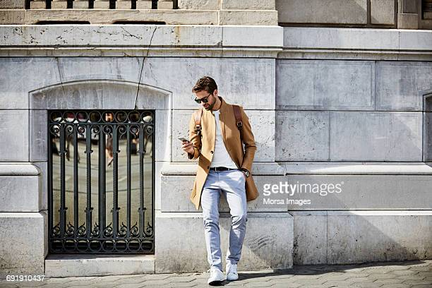 Businessman using phone while leaning on wall