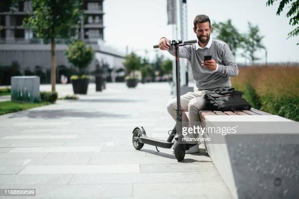 geschäftsmann mit telefon, während auf elektroroller - elektronik industrie stock-fotos und bilder