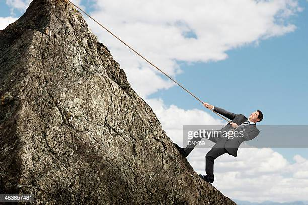 Businessman using rope to pull himself up steep mountain top