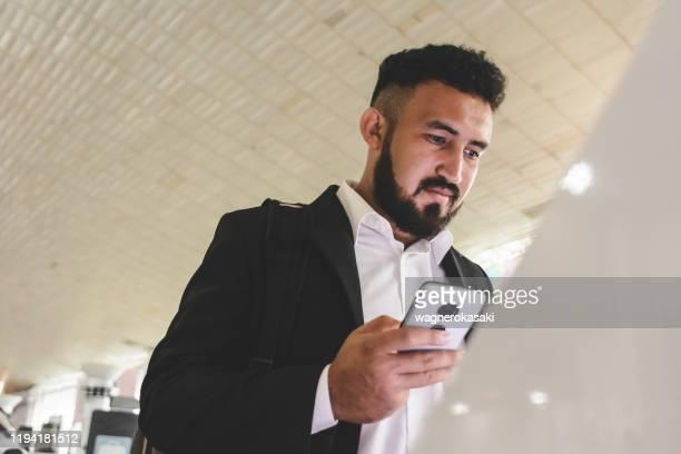 空港でセルフサービスチェックインを利用するビジネスマン - セルフサービス ストックフォトと画像