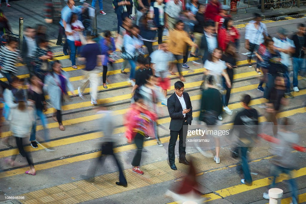 Businessman using smart phone amidst crowd : Stock Photo