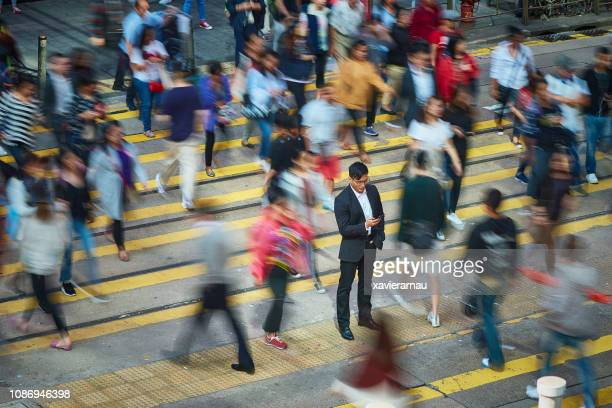 businessman using smart phone amidst crowd - velocità foto e immagini stock
