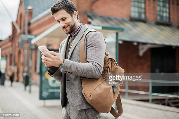 businessman using smart phone at bus station - transportation building type of building stock photos and pictures