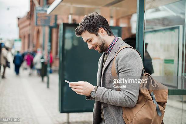 businessman using smart phone at bus station - wachten stockfoto's en -beelden
