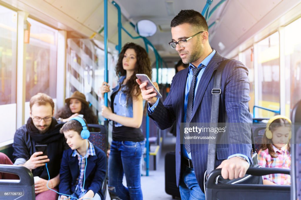 Businessman using smart phone in a bus : Stock Photo