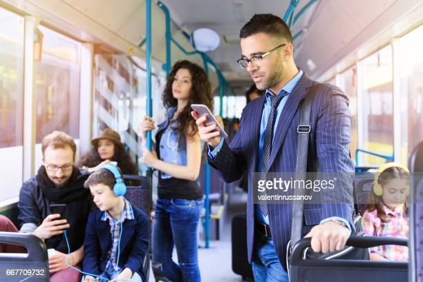 Businessman using smart phone in a bus