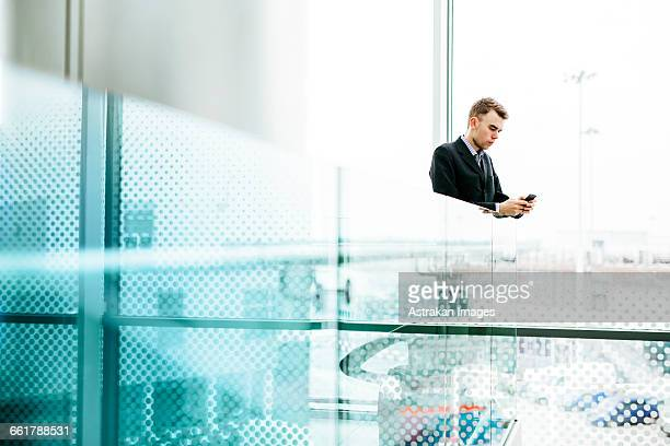Businessman using smart phone in airport