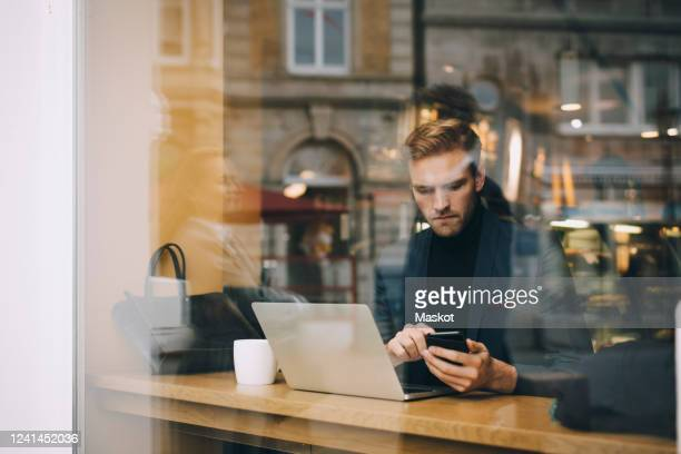 businessman using smart phone in cafe seen through glass window - formalwear stock pictures, royalty-free photos & images