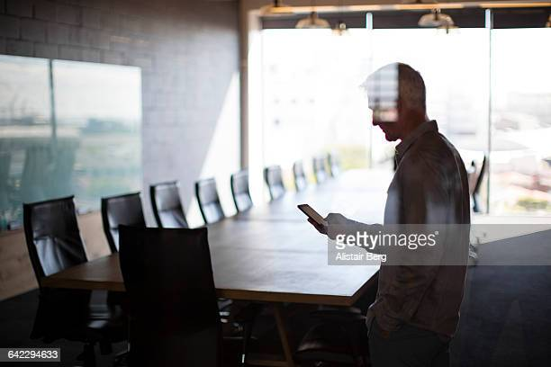 businessman using smart phone in conference room - licht natuurlijk fenomeen stockfoto's en -beelden