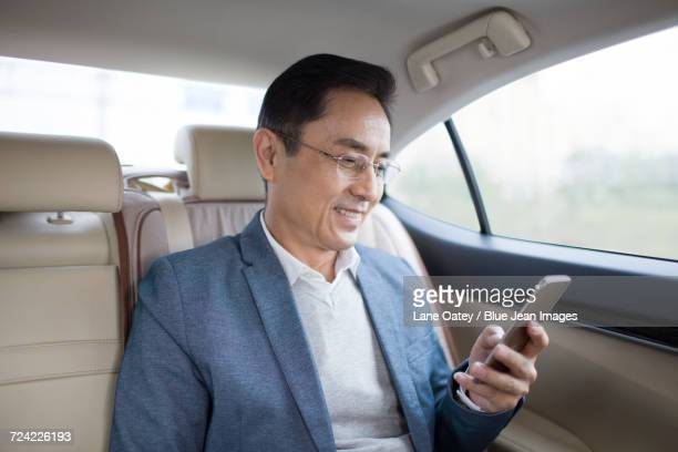 Businessman using smart phone inside car