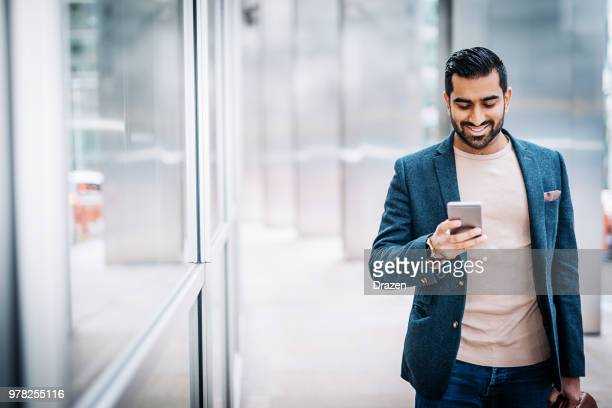 businessman using smart phone near office building - indian subcontinent ethnicity stock pictures, royalty-free photos & images