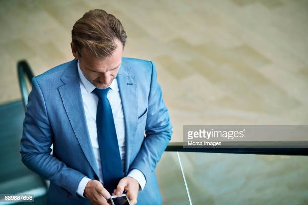 Businessman using smart phone on escalator