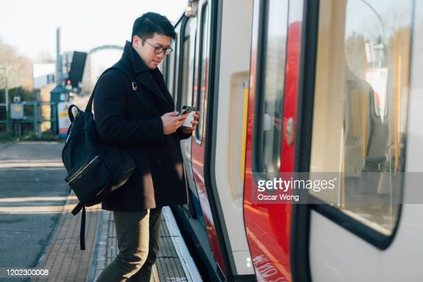 businessman using smart phone on the train platform - one man only stock pictures, royalty-free photos & images