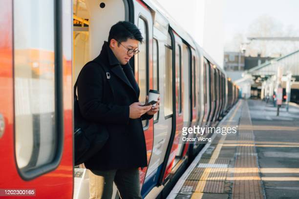 businessman using smart phone on the train platform - commuter stock pictures, royalty-free photos & images